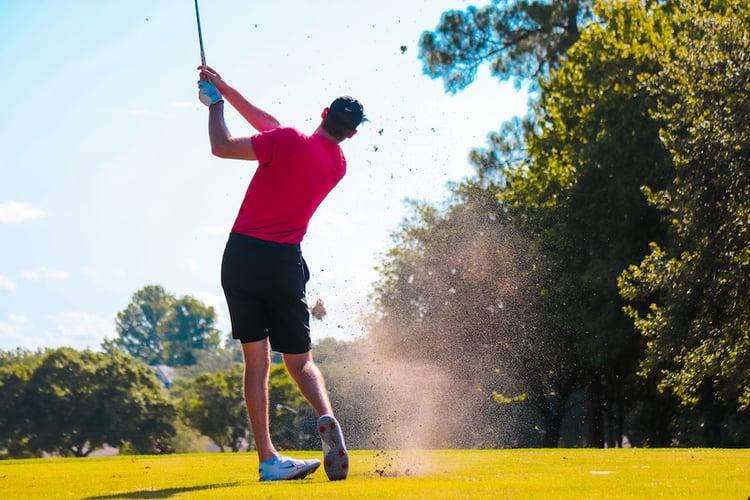 golfer swinging club trees grass green blue sky golf